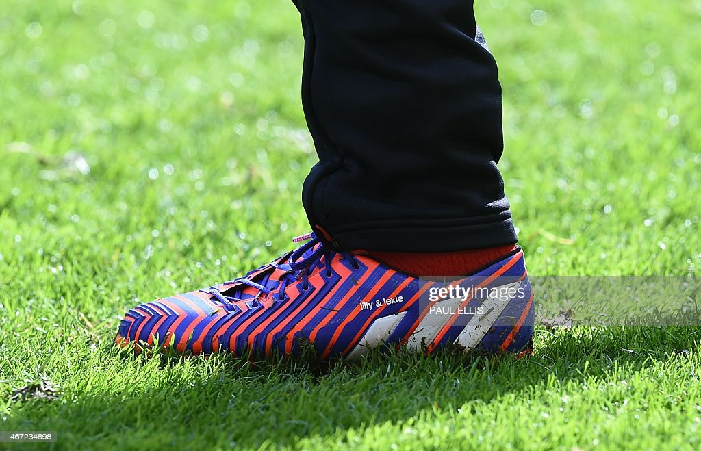 Liverpool's English midfielder Steven Gerrard's boots with his daughters names clearly seen during warm up ahead of the English Premier League football match between Liverpool and Manchester United at Anfield in Liverpool, north west England on March 22, 2015. AFP PHOTO / PAUL ELLIS