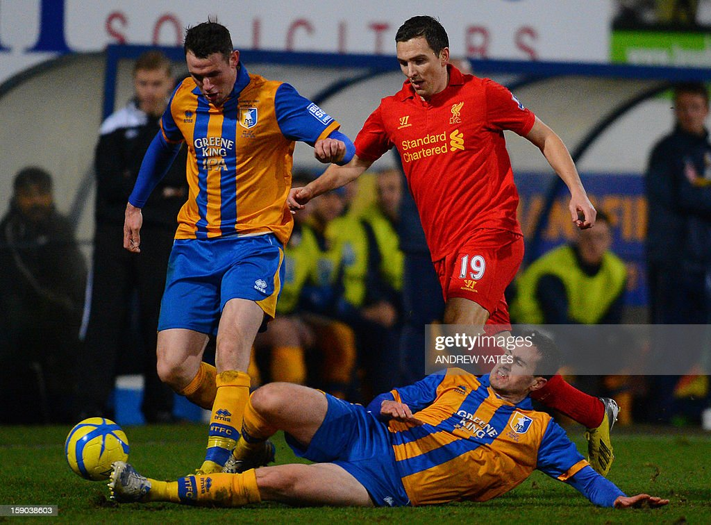 "Liverpool's English midfielder Stewart Downing (R) vies with Mansfield Town's Welsh defender Lee Beevers (L) and English midfielder Chris Clements (ground) during the FA Cup third round football match between Mansfield Town and Liverpool at Field Mill in Mansfield, central England, on January 6, 2013. Liverpool won the match 2-1. USE. No use with unauthorized audio, video, data, fixture lists, club/league logos or ""live"" services. Online in-match use limited to 45 images, no video emulation. No use in betting, games or single club/league/player publications."