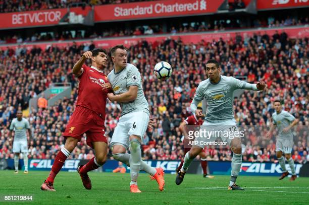 Liverpool's English striker Dominic Solanke vies with Manchester United's English defender Phil Jones and Manchester United's English defender Chris...