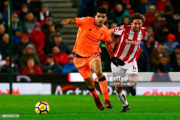 Liverpool's English striker Dominic Solanke vies with Stoke City's Welsh midfielder Joe Allen during the English Premier League football match...