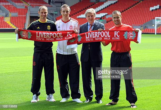 Liverpool's football club's manager Roy Hodgson poses for photographers with new signings Milan Jovanovic of Serbia Danny Wilson of Scotland and Joe...