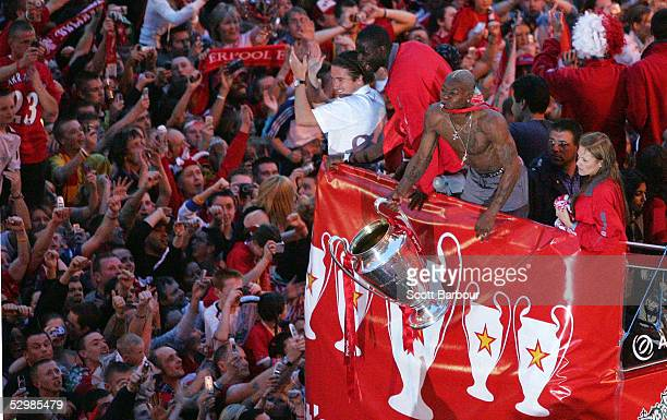 Liverpool's French striker Djibril Cisse celebrates with the trophy as the Liverpool team rides on an open top bus through a mass of fans as they...