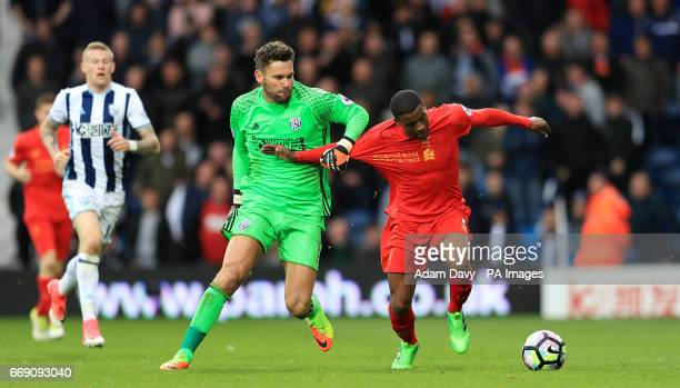 Liverpool's Georginio Wijnaldum battles with West Bromwich Albion goalkeeper Ben Foster near the halfway line in the dying moments of the game during...