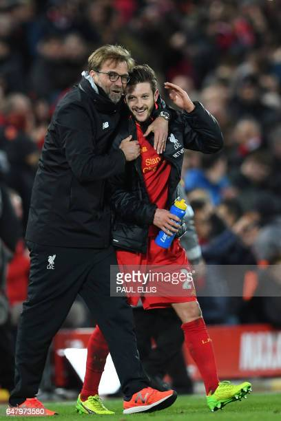 Liverpool's German manager Jurgen Klopp celebrates on the pitch with Liverpool's English midfielder Adam Lallana after the English Premier League...