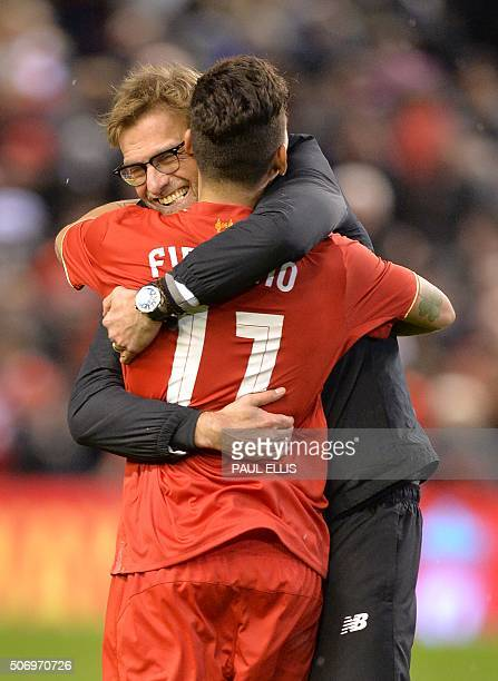 Liverpool's German manager Jurgen Klopp embraces Liverpool's Brazilian midfielder Roberto Firmino after winning the penalty shootout in the English...