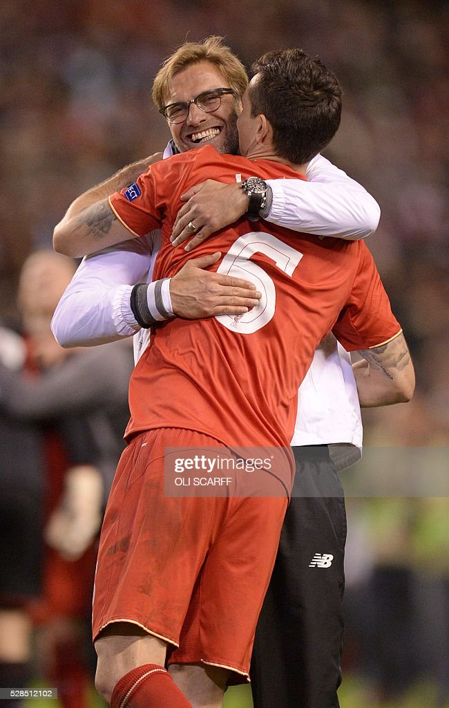 Liverpool's German manager Jurgen Klopp (Facing) embraces Liverpool's Croatian defender Dejan Lovren after a 3-0 victory during the UEFA Europa League semi-final second leg football match between Liverpool and Villarreal CF at Anfield in Liverpool, northwest England on May 5, 2016. / AFP / OLI