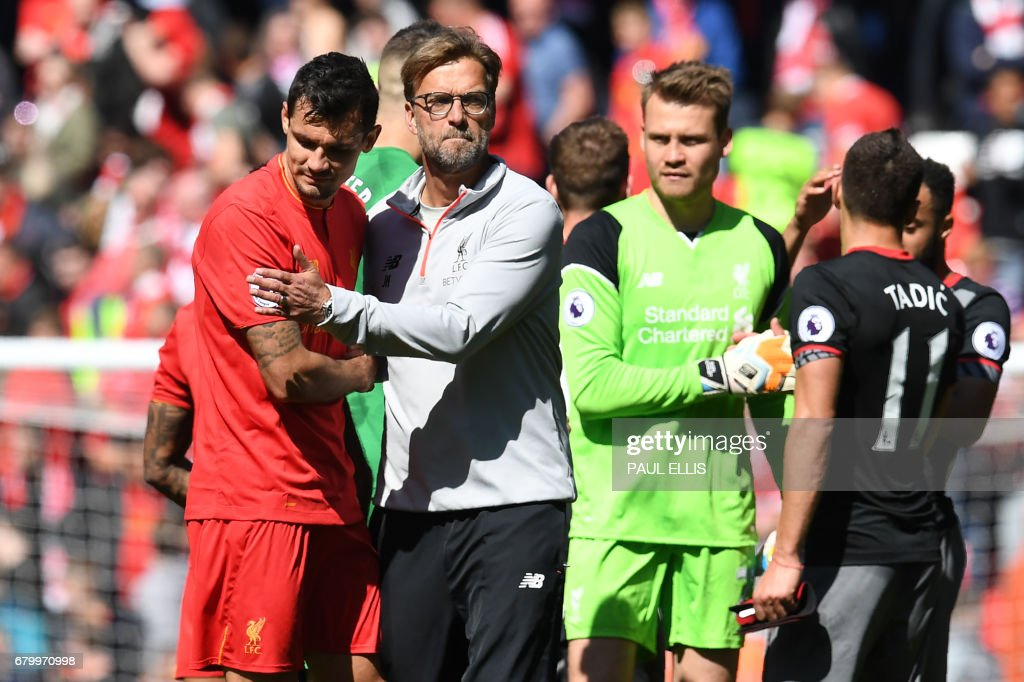 Liverpool's German manager Jurgen Klopp (C) embraces Liverpool's Croatian defender Dejan Lovren after the English Premier League football match between Liverpool and Southampton at Anfield in Liverpool, north west England on May 7, 2017. / AFP PHOTO / Paul ELLIS / RESTRICTED TO EDITORIAL USE. No use with unauthorized audio, video, data, fixture lists, club/league logos or 'live' services. Online in-match use limited to 75 images, no video emulation. No use in betting, games or single club/league/player publications. /