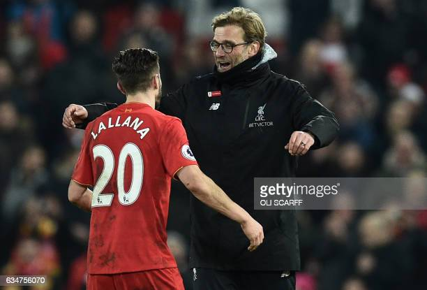 Liverpool's German manager Jurgen Klopp embraces Liverpool's English midfielder Adam Lallana on the pitch after the English Premier League football...