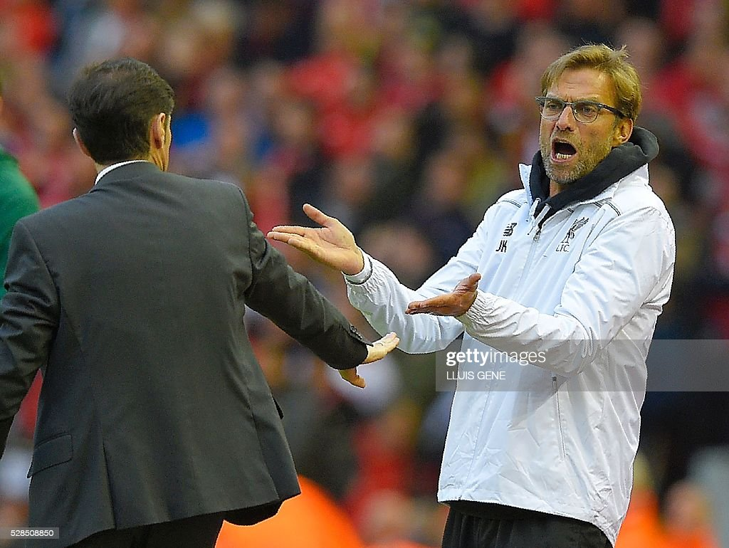 Liverpool's German manager Jurgen Klopp (L) gestures towards Villarreal's coach Marcelino Garcia Toral during the UEFA Europa League semi-final second leg football match between Liverpool and Villarreal CF at Anfield in Liverpool, northwest England on May 5, 2016. / AFP / LLUIS