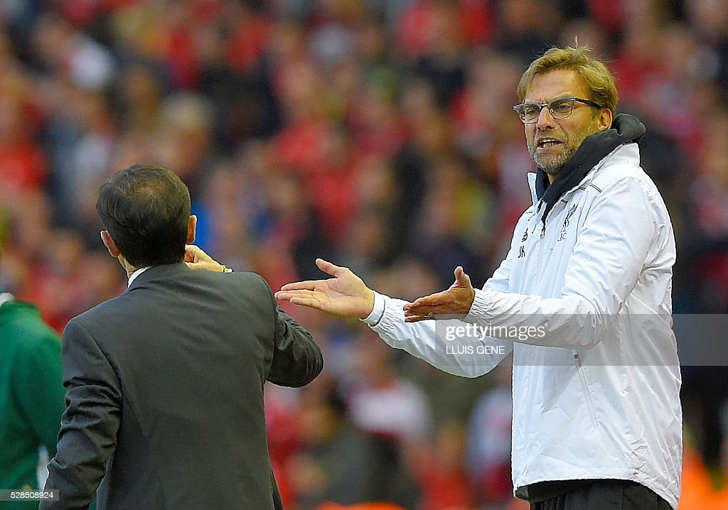 Liverpool's German manager Jurgen Klopp (R) gestures towards Villarreal's coach Marcelino Garcia Toral during the UEFA Europa League semi-final second leg football match between Liverpool and Villarreal CF at Anfield in Liverpool, northwest England on May 5, 2016. / AFP / LLUIS