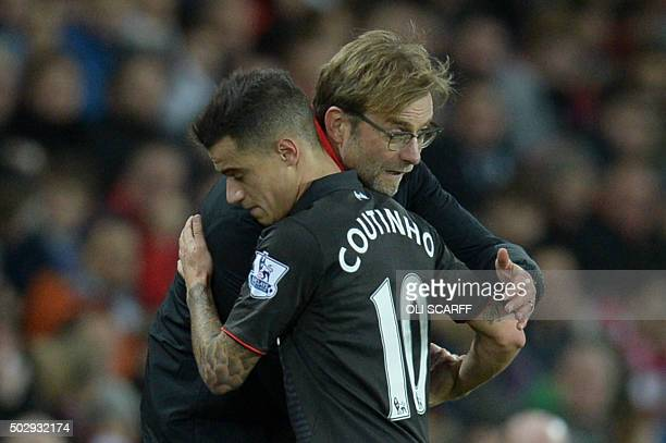Liverpool's German manager Jurgen Klopp hugs Liverpool's Brazilian midfielder Philippe Coutinho as Coutinho leaves the field after being substituted...
