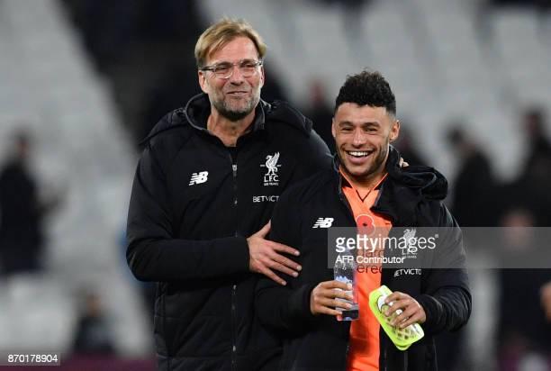 Liverpool's German manager Jurgen Klopp jokes with Liverpool's English midfielder Alex OxladeChamberlain after winning the English Premier League...