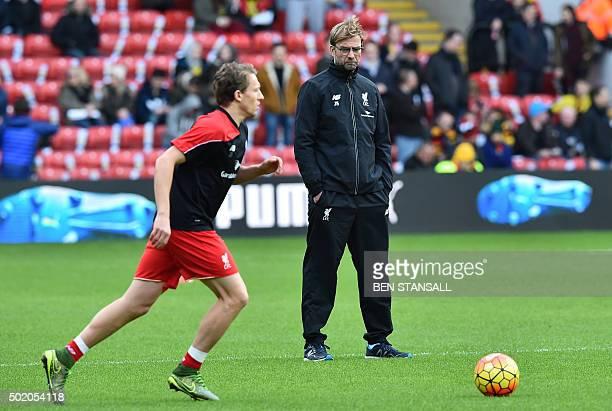 Liverpool's German manager Jurgen Klopp looks on as Liverpool's Brazilian midfielder Lucas Leiva warms up ahead of the English Premier League...