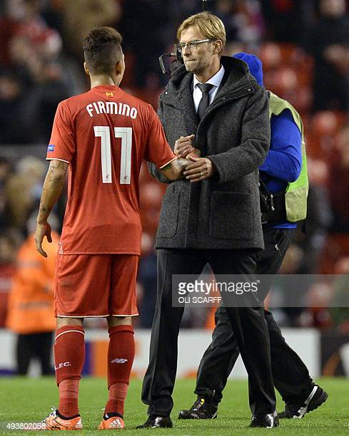 Liverpool's German manager Jurgen Klopp shakes hands with Liverpool's Brazilian midfielder Roberto Firmino after a UEFA Europa League group B...