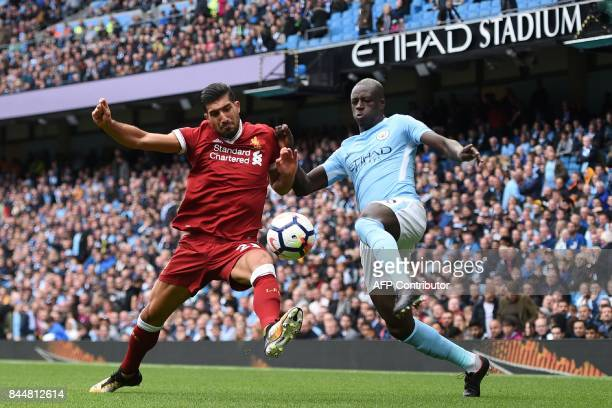 Liverpool's German midfielder Emre Can vies with Manchester City's French defender Benjamin Mendy during the English Premier League football match...