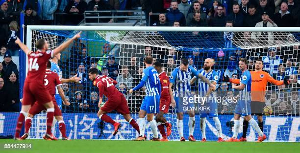 Liverpool's German midfielder Emre Can wheels away to celebrate after scoring the opening goal past Brighton's Australian goalkeeper Mathew Ryan...