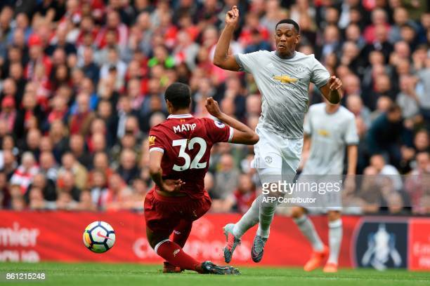Liverpool's Germanborn Cameroonian defender Joel Matip vies with Manchester United's French striker Anthony Martial during the English Premier League...