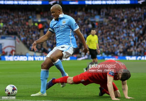 Liverpool's James Milner and Manchester City's Vincent Kompany battle for the ball
