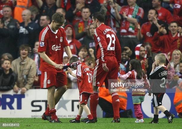 Liverpool's Jamie Carragher and his children with team mate Steven Gerrard during the lap of honour after the final whistle