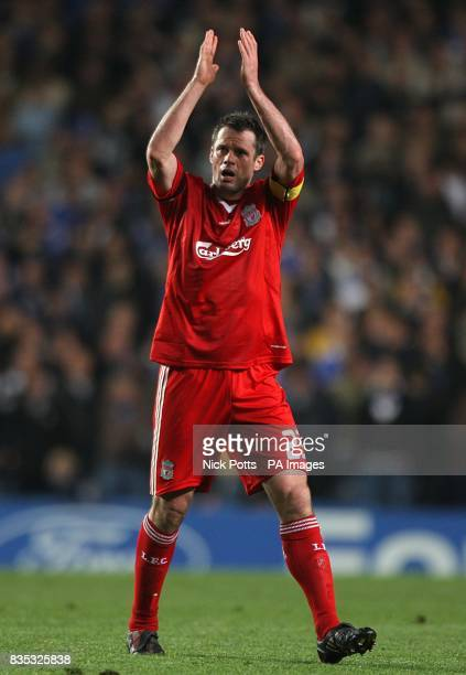 Liverpool's Jamie Carragher applauds the away fans as he leaves the field of play at half time