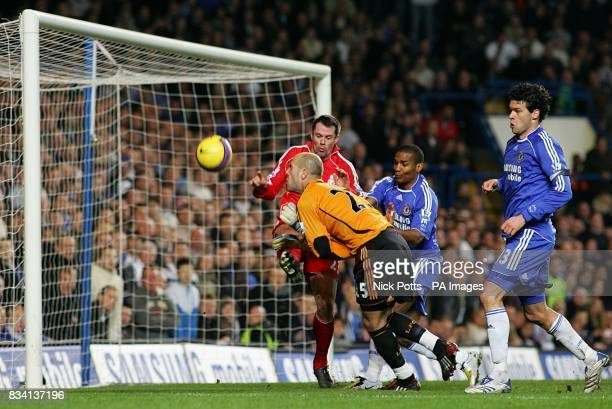 Liverpool's Jamie Carragher clears the ball off the line to help out goalkeeper Jose Reina as Chelsea's Michael Ballack and Florent Malouda close in...