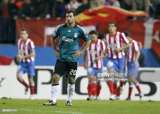 Liverpool's Javier Mascherano stands dejected after Athletico Madrid's Sabrosa Simao celebrates after scoring the equaliser