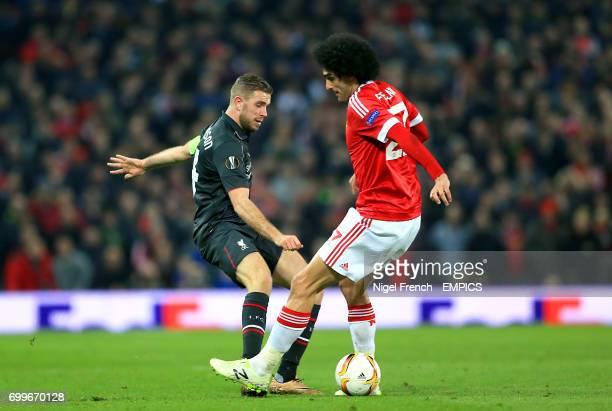 Liverpool's Jordan Henderson and Manchester United's Marouane Fellaini battle for the ball