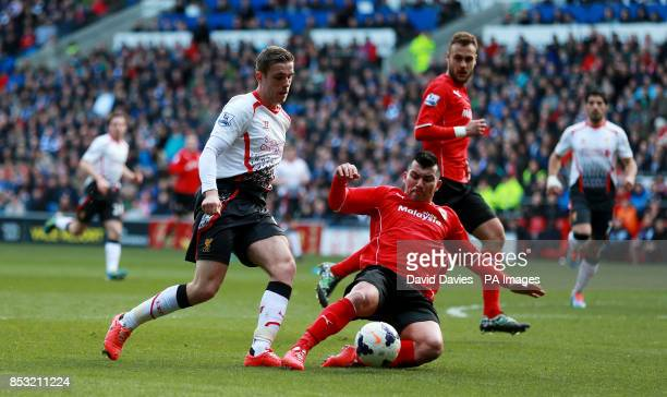 Liverpool's Jordan Henderson is tackled by Cardiff's Gary Medel during the Barclays Premier League match at Cardiff City Stadium Cardiff