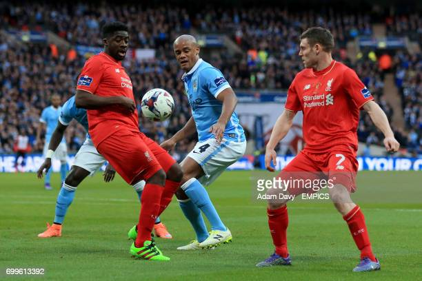 Liverpool's Kolo Toure and James Milner battle for the ball with Manchester City's Vincent Kompany