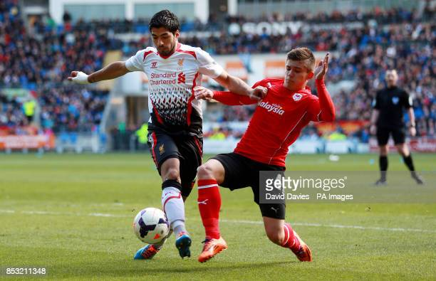 Liverpool's Luis Suarez is tackled by Cardiff's Declan John during the Barclays Premier League match at Cardiff City Stadium Cardiff