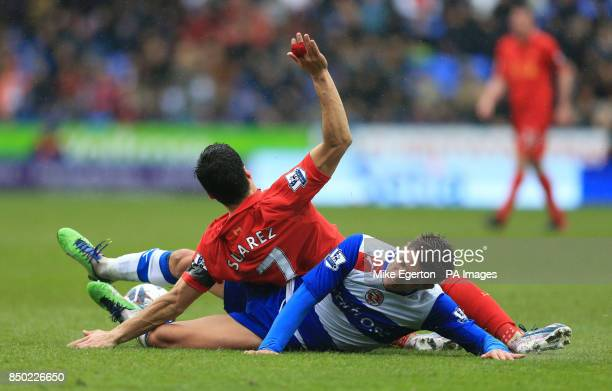 Liverpool's Luis Suarez is tackled by Reading's Daniel Carrico during the Barclays Premier League match at the Madejski Stadium Reading