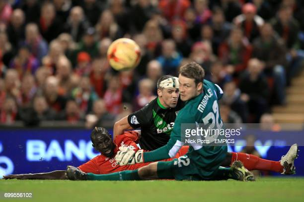 Liverpool's Mamadou Sakho challenges Stoke City's Jonathan Walters as he attempts a shot past Liverpool goalkeeper Simon Mignolet