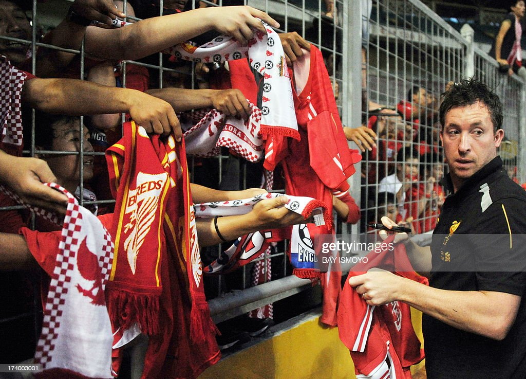 Liverpool's manager and former striker Robbie Fowler signs autographs to fans during a practice session at Bung Karno stadium in Jakarta on July 19, 2013 before their friendly match against Indonesian national team July 20, 2013. Rodgers said that Liverpool's striker Luis Suarez was not for sale, after the club reportedly turned down a 30 million pound deal from Arsenal. AFP PHOTO / Bay ISMOYO