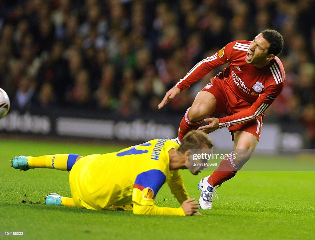 Liverpool's Maxi Rodriguez is caught by Octavian Abrudan of Steau Bucharest during the first leg UEFA Europa League match between Liverpool and Steau Bucharest on September 16, 2010 in Liverpool, England.