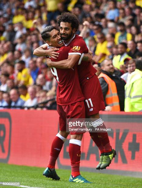 Liverpool's Mohamed Salah celebrates scoring his side's third goal with teammate Roberto Firmino during the Premier League match at Vicarage Road...