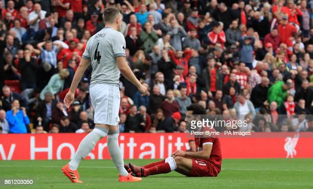 Liverpool's Mohamed Salah sits on the ground during the Premier League match at Anfield Liverpool