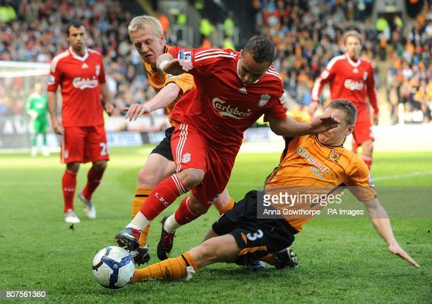 Liverpool's Nabil El Zhar is challenged by Hull City's Andy Dawson and Mark Cullen