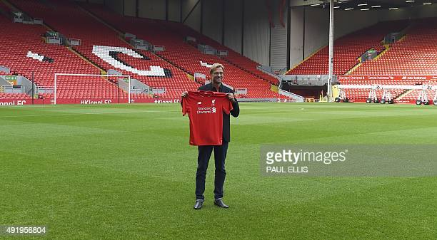 Liverpool's new German manager Jurgen Klopp poses with a team jersey on the pitch after a press conference to announce his new appointment at Anfield...
