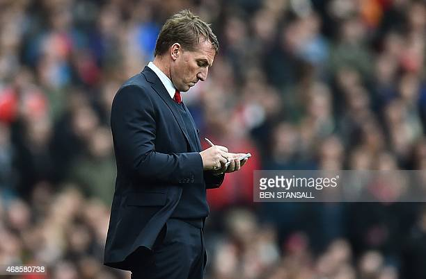 Liverpool's Northern Irish manager Brendan Rodgers makes notes during the English Premier League football match between Arsenal and Liverpool at the...