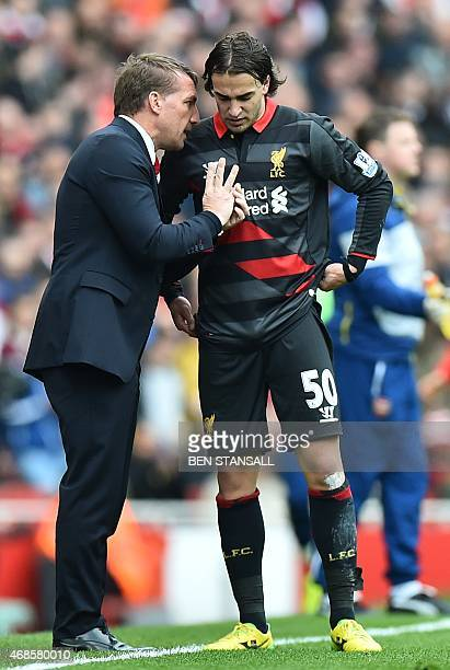 Liverpool's Northern Irish manager Brendan Rodgers speaks with Liverpool's Serbian midfielder Lazar Markovic during the English Premier League...