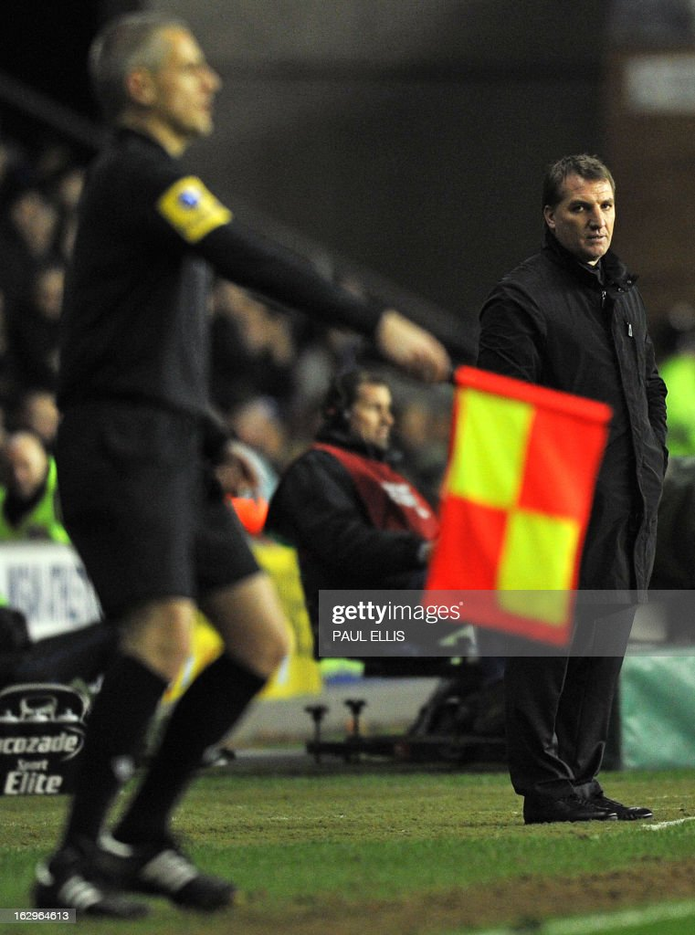 Liverpool's Northern Irish manager Brendan Rodgers (R) watches as the assistant referee signals for offside during the English Premier League football match between Wigan Athletic and Liverpool at The DW Stadium in Wigan, northwest England, on March 2, 2013. USE. No use with unauthorized audio, video, data, fixture lists, club/league logos or 'live' services. Online in-match use limited to 45 images, no video emulation. No use in betting, games or single club/league/player publications.
