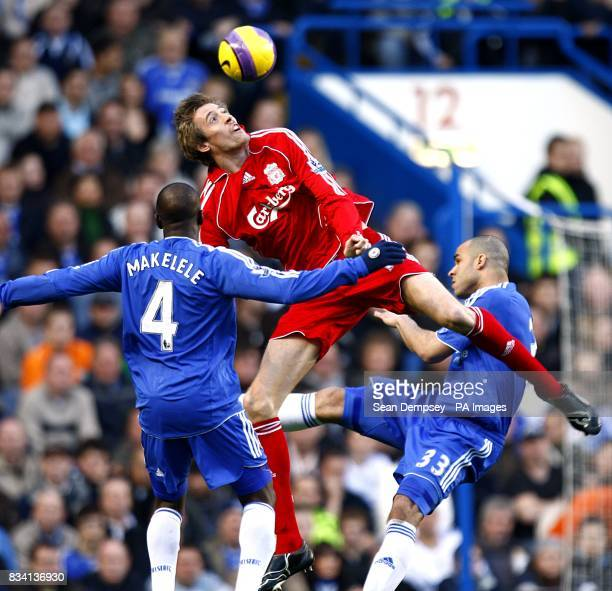 Liverpool's Peter Crouch is challenged in the air by Chelsea's Claude Makelele and Alex