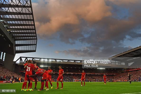 Liverpool's players celebrate together after Firmino scores their fourth goal during the English Premier League football match between Liverpool and...
