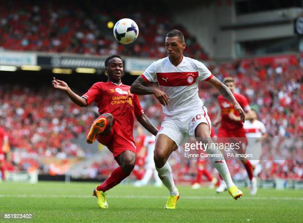 Liverpool's Raheem Sterling and Olmpicacos's Jose Holebas in action during the friendly at Anfield Liverpool