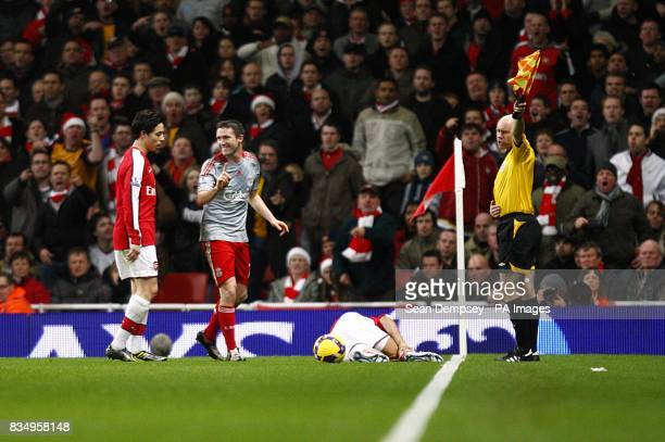 Liverpool's Robbie Keane gestures towards Arsenal's Samir Nasri after fouling Gael Clichy