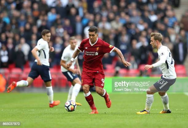 Liverpool's Roberto Firmino and Tottenham Hotspur's Christian Eriksen battle for the ball during the Premier League match at the Wembley Stadium...