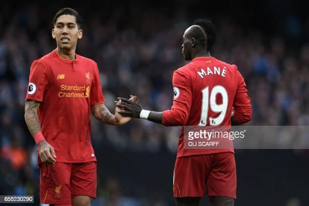 Liverpool's Senegalese midfielder Sadio Mane gestures to Liverpool's Brazilian midfielder Roberto Firmino during the English Premier League football...