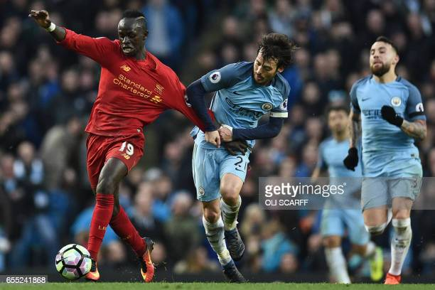 Liverpool's Senegalese midfielder Sadio Mane is held back by Manchester City's Spanish midfielder David Silva during the English Premier League...