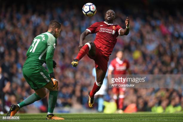 Liverpool's Senegalese midfielder Sadio Mane is sent off for this challenge on Manchester City's Brazilian goalkeeper Ederson during the English...