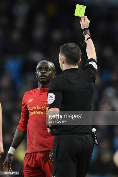 Liverpool's Senegalese midfielder Sadio Mane is shown a yellow card by English referee Michael Oliver during the English Premier League football...